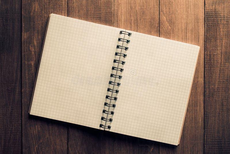 ελεγχμένο σημειωματάριο στο ξύλο στοκ φωτογραφία