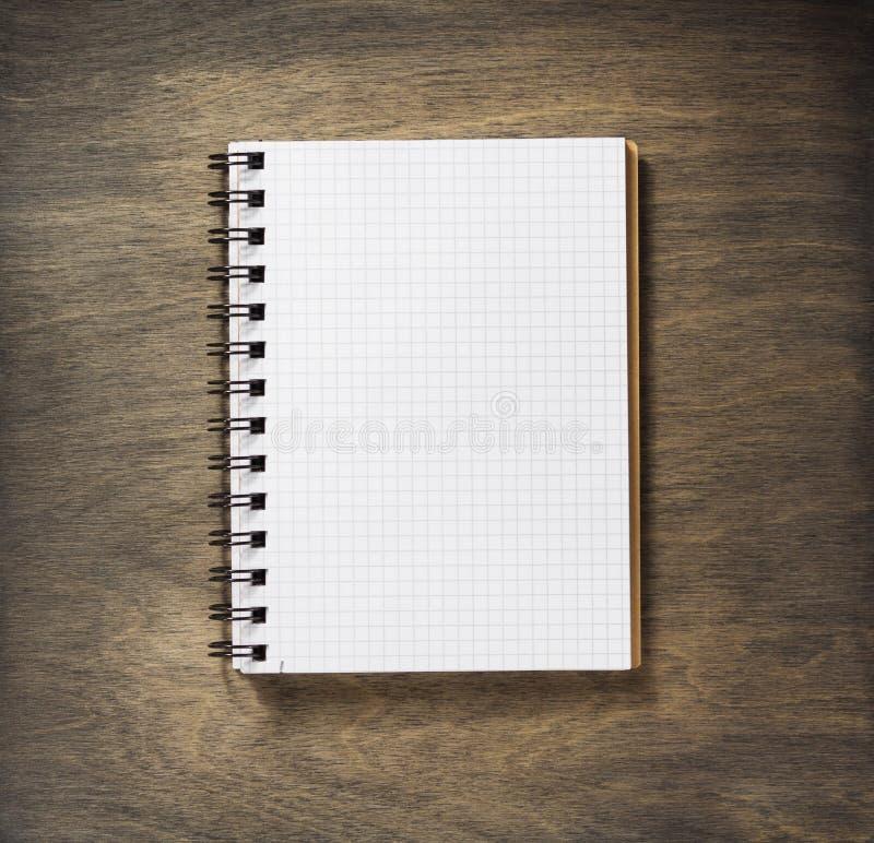 Ελεγχμένο σημειωματάριο στο ξύλο στοκ εικόνα