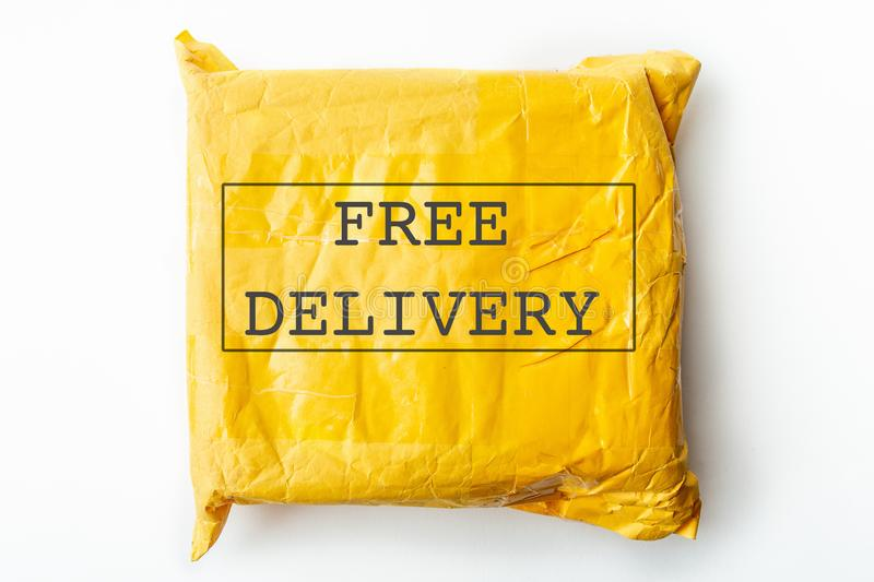 ΕΛΕΥΘΕΡΟ κείμενο ΠΑΡΑΔΟΣΗΣ στην κίτρινο συσκευασία δεμάτων ή το κιβώτιο φορτίου με το προϊόν, δωρεάν λογιστικές ναυτιλία και διαν στοκ φωτογραφία