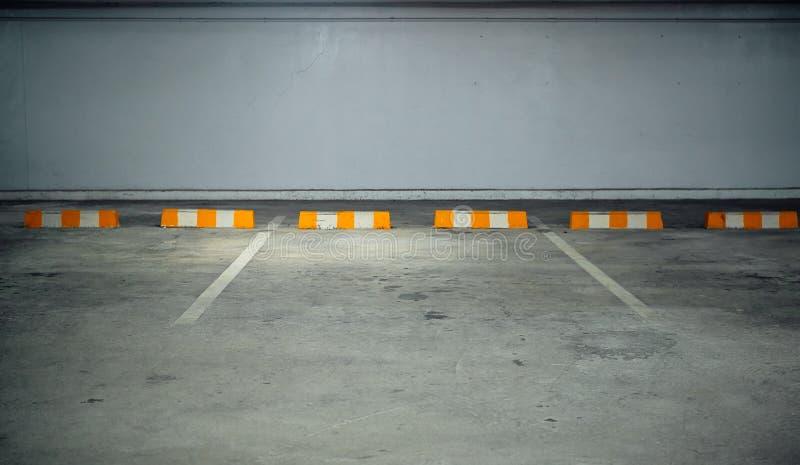 Ελεύθερος χώρος στάθμευσης -οικοδόμησης με τα κίτρινα άσπρα εμπόδια στοκ εικόνα