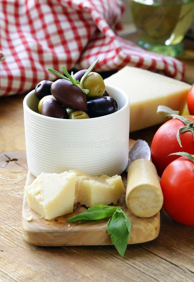 Ελιές, τυρί παρμεζάνας, ντομάτες και βασιλικός στοκ εικόνα