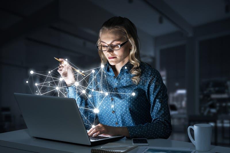 Ελκυστικά ξανθά φορώντας γυαλιά στο σκοτεινό γραφείο που χρησιμοποιεί το lap-top Μικτά μέσα στοκ φωτογραφία με δικαίωμα ελεύθερης χρήσης