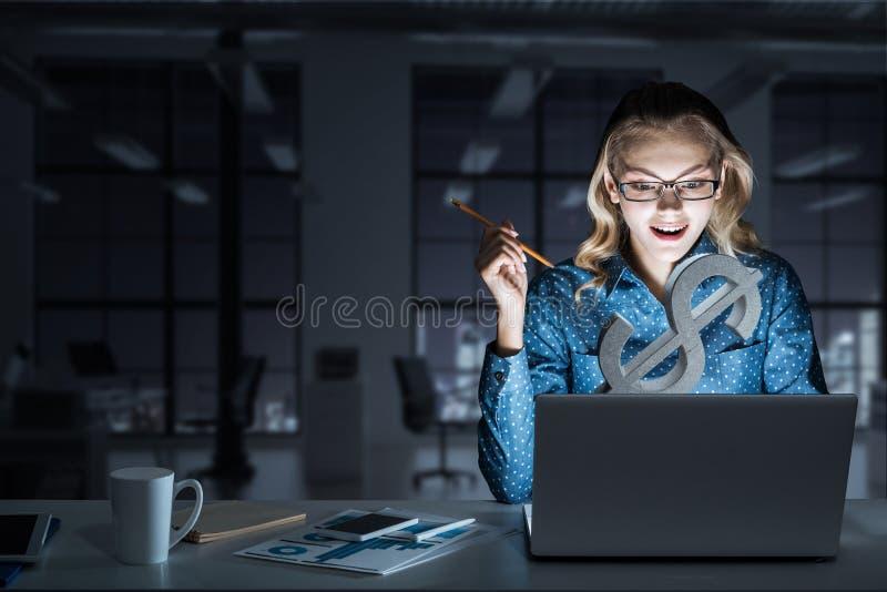 Ελκυστικά ξανθά φορώντας γυαλιά στο σκοτεινό γραφείο που χρησιμοποιεί το lap-top Μικτά μέσα στοκ φωτογραφία