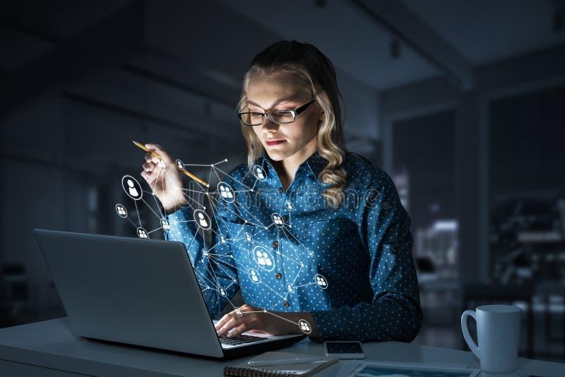 Ελκυστικά ξανθά φορώντας γυαλιά στο σκοτεινό γραφείο που χρησιμοποιεί το lap-top Μικτά μέσα στοκ εικόνα με δικαίωμα ελεύθερης χρήσης