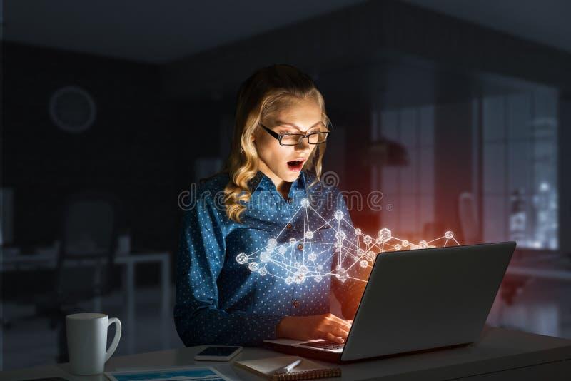 Ελκυστικά ξανθά φορώντας γυαλιά στο σκοτεινό γραφείο που χρησιμοποιεί το lap-top r στοκ εικόνες με δικαίωμα ελεύθερης χρήσης