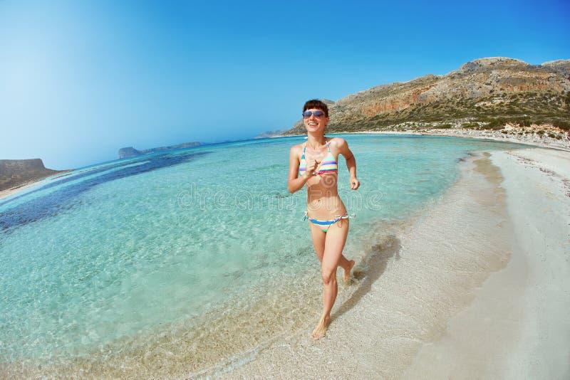 Ελκυστικά τρεξίματα γυναικών στην παραλία κατά μήκος της ακτής στοκ εικόνες