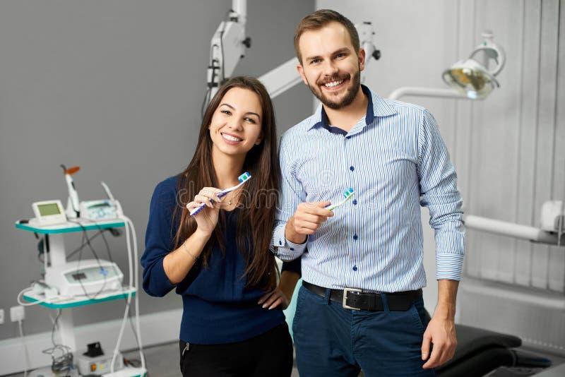Ελκυστικές οδοντόβουρτσες εκμετάλλευσης ζευγών με την κόλλα στο οδοντικό γραφείο στοκ εικόνες
