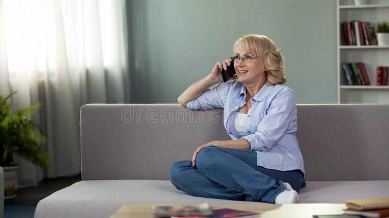 Ελκυστική ανώτερη συνεδρίαση γυναικών στον καναπέ και κλήση της κόρης, επικοινωνία στοκ εικόνα