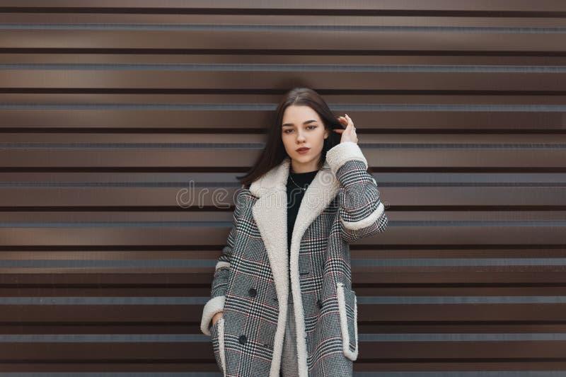 Ελκυστική αρκετά νέα γυναίκα σε ένα κομψό ελεγμένο παλτό με την άσπρη γούνα σε μια μαύρη μοντέρνη μπλούζα στην γκρίζα τοποθέτηση  στοκ φωτογραφίες