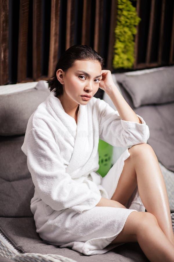 Ελκυστική ασιατική γυναικεία συνεδρίαση στο σαλόνι και τοποθέτηση στο ασβέστιο στοκ εικόνες