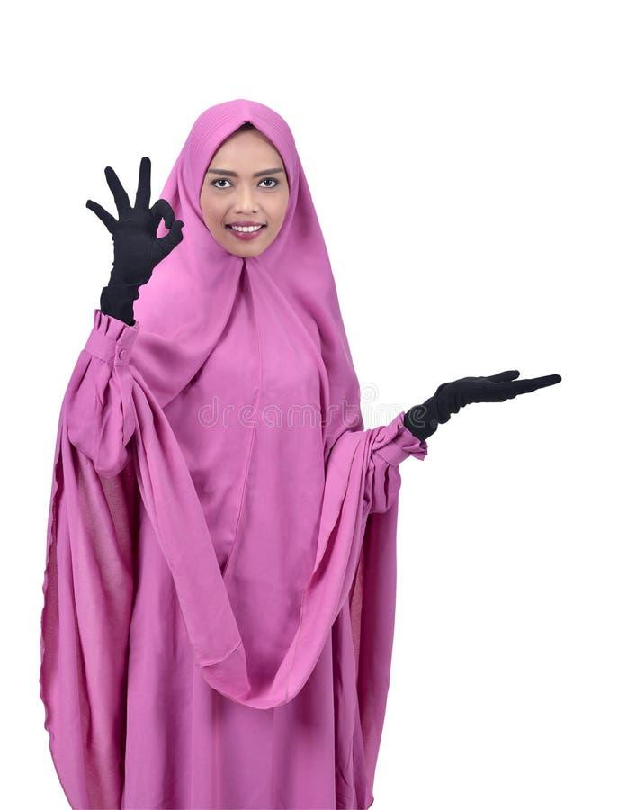 Ελκυστική ασιατική μουσουλμανική γυναίκα που παρουσιάζει κενό διάστημα για το copyspace στοκ φωτογραφία με δικαίωμα ελεύθερης χρήσης