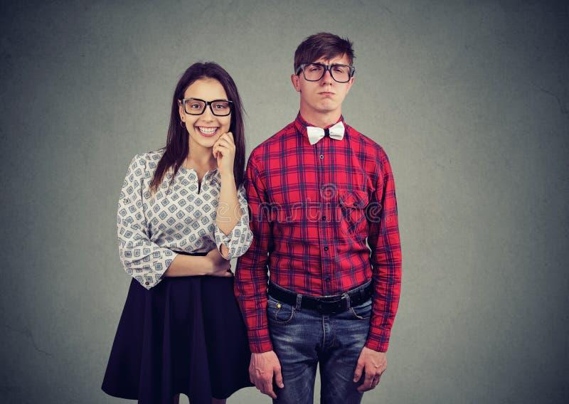 Ελκυστική γοητευτική γυναίκα που χρονολογεί με το nerd στην ντεμοντέ eyewear και εκκεντρική ένδυση στοκ εικόνα