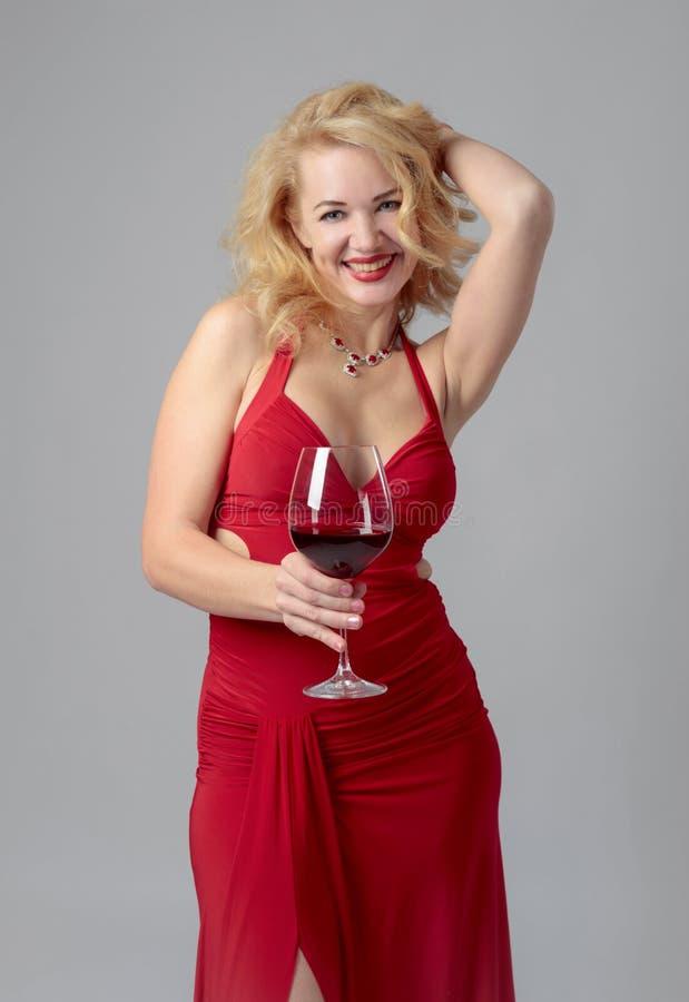 Ελκυστική γυναίκα Μεσαίωνα στο κόκκινο φόρεμα βραδιού με το ποτήρι του κόκκινου κρασιού στοκ εικόνα με δικαίωμα ελεύθερης χρήσης