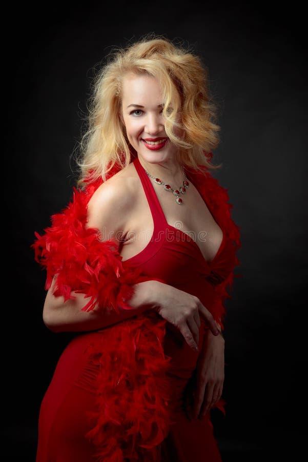 Ελκυστική γυναίκα Μεσαίωνα στο κόκκινο φόρεμα βραδιού με χνουδωτό boa φτερών στοκ φωτογραφία με δικαίωμα ελεύθερης χρήσης