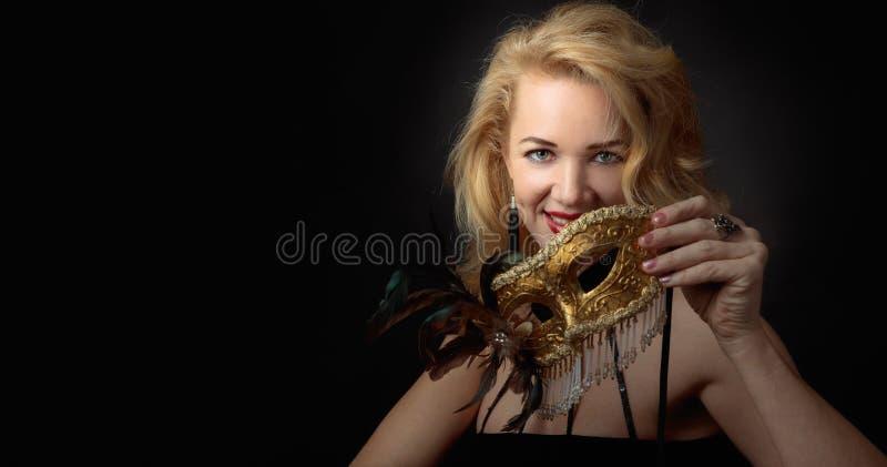 Ελκυστική γυναίκα Μεσαίωνα στο μαύρο φόρεμα βραδιού με τη χρυσή μάσκα καρναβαλιού στοκ φωτογραφία με δικαίωμα ελεύθερης χρήσης