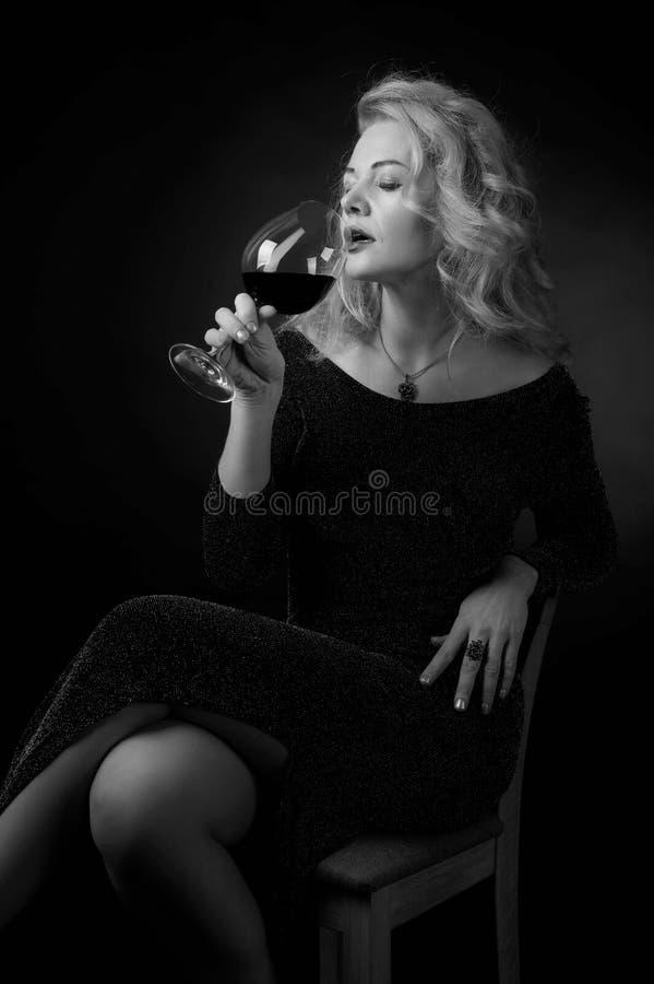 Ελκυστική γυναίκα Μεσαίωνα στο μαύρο φόρεμα βραδιού με το ποτήρι του κόκκινου κρασιού στοκ εικόνες