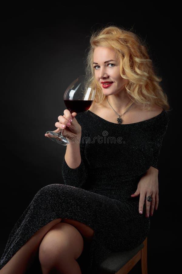 Ελκυστική γυναίκα Μεσαίωνα στο μαύρο φόρεμα βραδιού με το ποτήρι του κόκκινου κρασιού στοκ φωτογραφίες