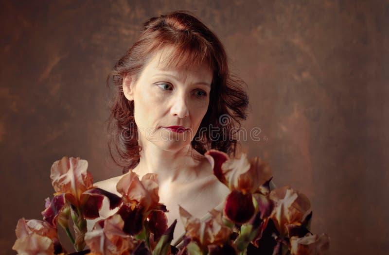 Ελκυστική γυναίκα με τα καφετιά άνθη ίριδων στοκ φωτογραφία με δικαίωμα ελεύθερης χρήσης