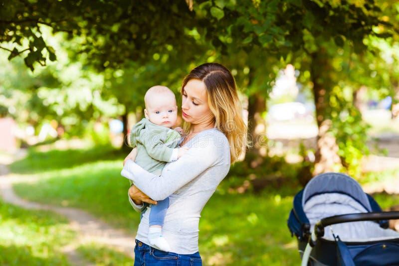 Ελκυστική γυναίκα με το γιο της στα όπλα της στοκ εικόνες