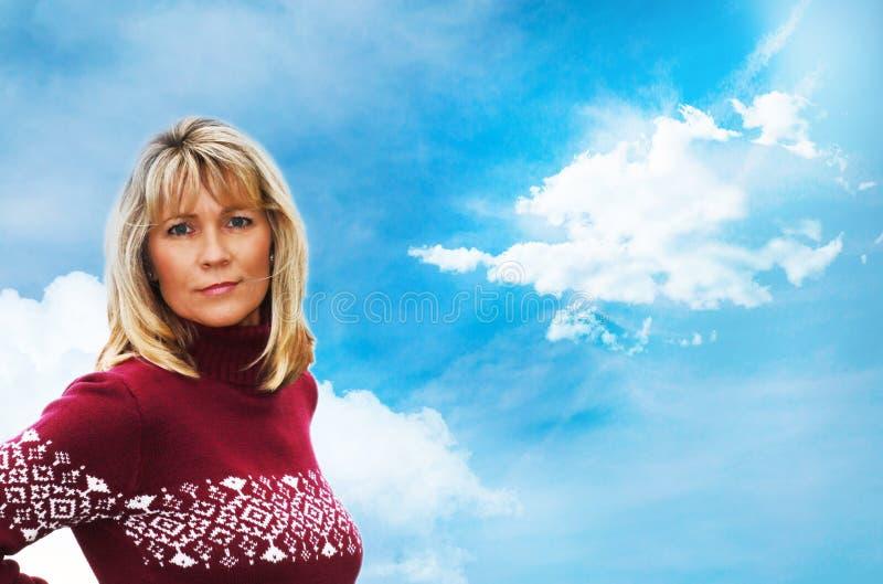 Ελκυστική γυναίκα με το πουλόβερ μπροστά από τον ουρανό στοκ εικόνες