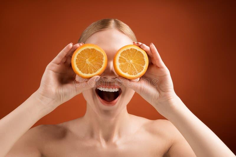 Ελκυστική γυναίκα που έχει τη διασκέδαση με τα φρούτα στοκ φωτογραφία