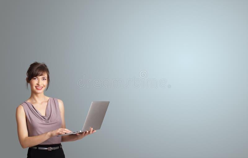 Ελκυστική γυναίκα που κρατά ένα lap-top με το διάστημα αντιγράφων στοκ εικόνα με δικαίωμα ελεύθερης χρήσης