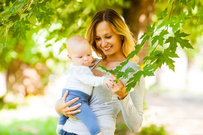 Ελκυστική γυναίκα που κρατά το μωρό της που παρουσιάζει φύλλα σε ένα δέντρο στοκ εικόνες με δικαίωμα ελεύθερης χρήσης