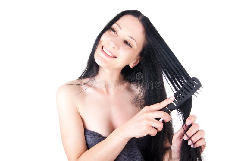 Ελκυστική γυναίκα που κτενίζει το τρίχωμά της στοκ εικόνα με δικαίωμα ελεύθερης χρήσης