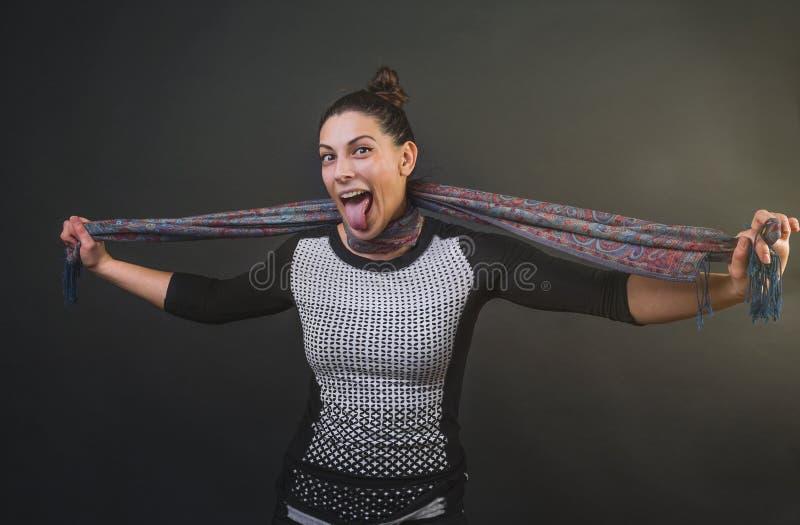 Ελκυστική γυναίκα που πνίγει την μόνη με ένα μαντίλι μεταξιού και που κολλά τη γλώσσα της έξω χαμογελώντας στοκ φωτογραφίες
