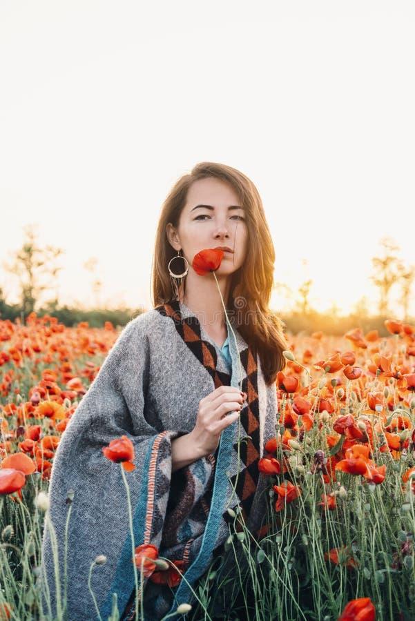 Ελκυστική γυναίκα που στέκεται με μια παπαρούνα στον τομέα στοκ εικόνα