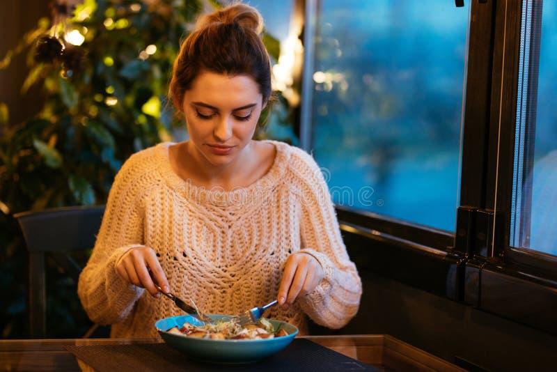 Ελκυστική γυναίκα που τρώει τη σαλάτα, που στηρίζεται στον καφέ στοκ φωτογραφίες με δικαίωμα ελεύθερης χρήσης
