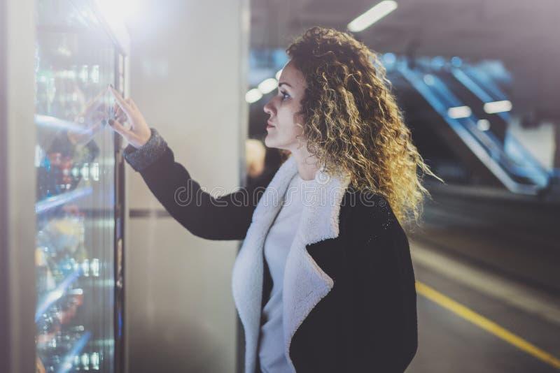 Ελκυστική γυναίκα στην πλατφόρμα διέλευσης που χρησιμοποιεί μια σύγχρονη μηχανή πώλησης ποτών Το χέρι της τοποθετείται στο μαξιλά στοκ φωτογραφίες