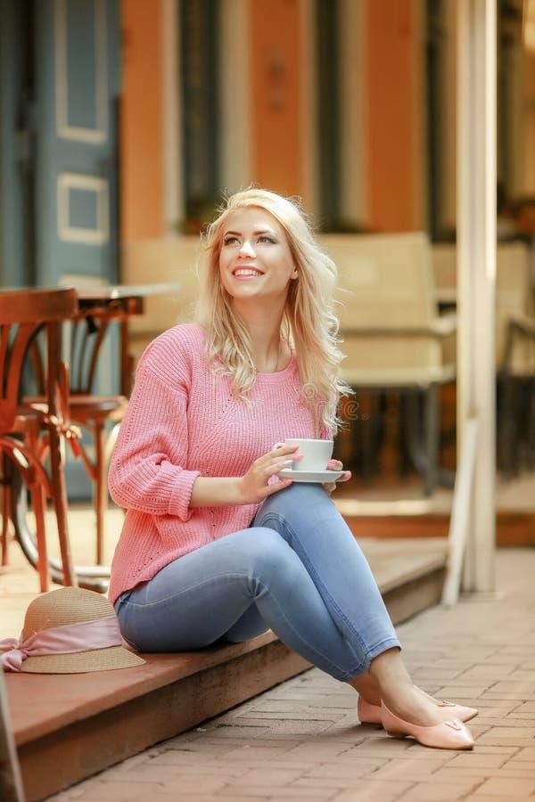 Ελκυστική γυναίκα στη ρομαντική διάθεση που χαμογελά στη συνεδρίαση ευτυχίας στον πίνακα που φορά το ρόδινο σακάκι, μοντέρνη ενδυ στοκ εικόνες
