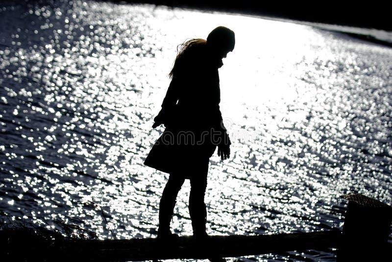 Ελκυστική γυναίκα στη σκιαγραφία λιμνών στοκ εικόνες