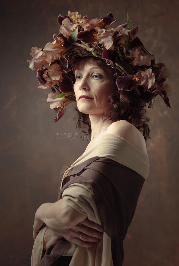 Ελκυστική γυναίκα στο στεφάνι με τα καφετιά άνθη ίριδων στοκ φωτογραφίες
