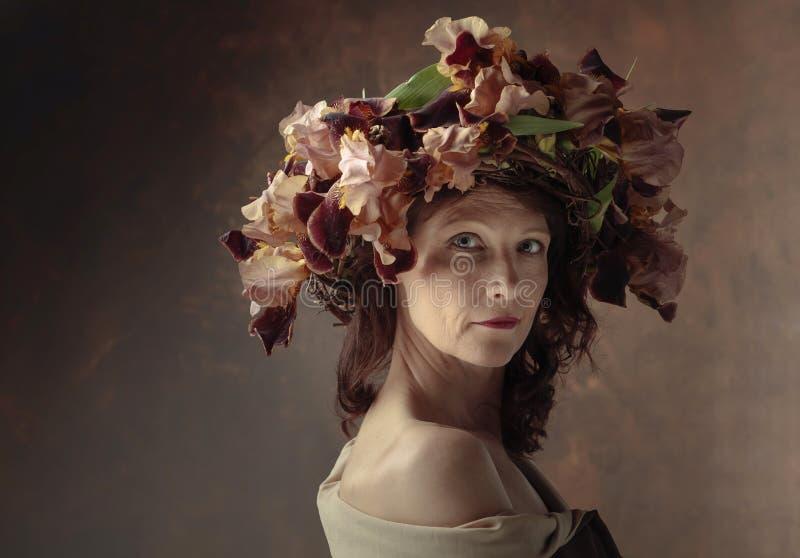 Ελκυστική γυναίκα στο στεφάνι με τα καφετιά άνθη ίριδων στοκ εικόνες με δικαίωμα ελεύθερης χρήσης