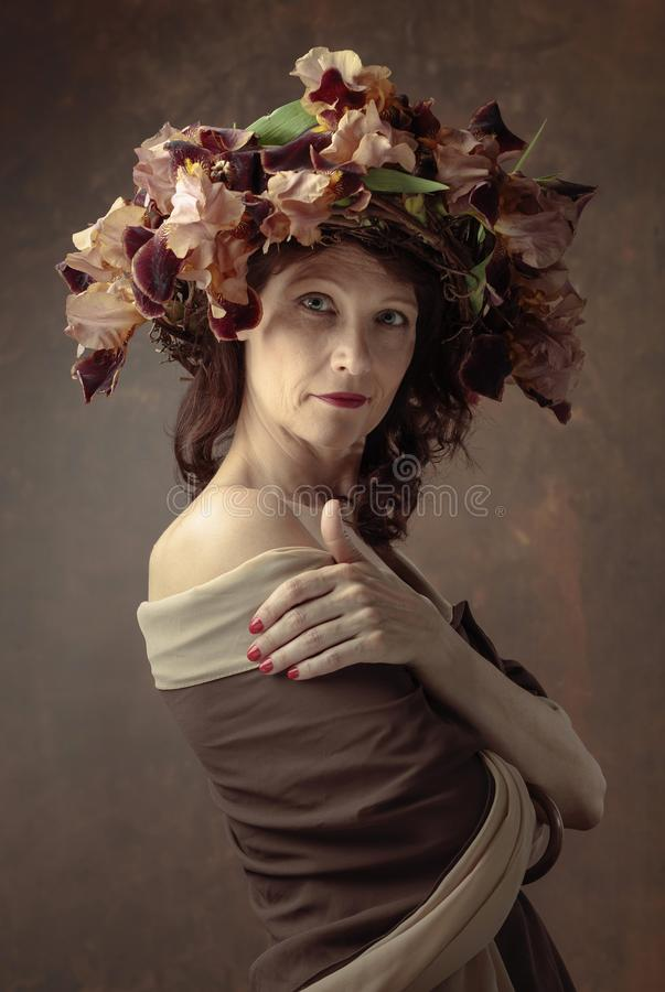 Ελκυστική γυναίκα στο στεφάνι με τα καφετιά άνθη ίριδων στοκ φωτογραφίες με δικαίωμα ελεύθερης χρήσης