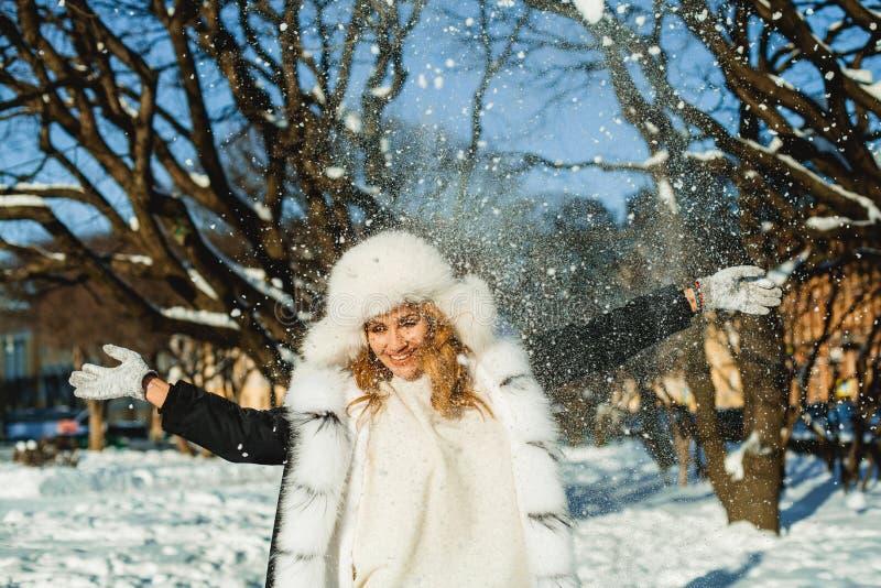 Ελκυστική γυναίκα στο χειμερινό παλτό που έχει τη διασκέδαση με το χιόνι στοκ εικόνα με δικαίωμα ελεύθερης χρήσης