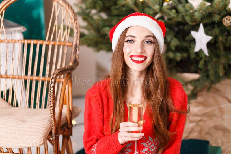 Ελκυστική γυναίκα Χριστουγέννων που φορά τη συνεδρίαση καπέλων Santa κοντά στις ερυθρελάτες στοκ φωτογραφία