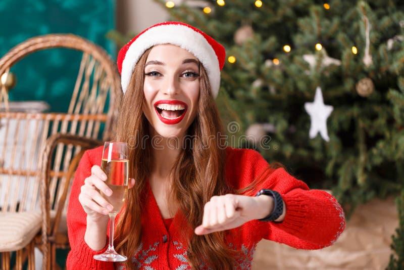Ελκυστική γυναίκα Χριστουγέννων που φορά το καπέλο Santa που περιμένει το νέο έτος στοκ εικόνες