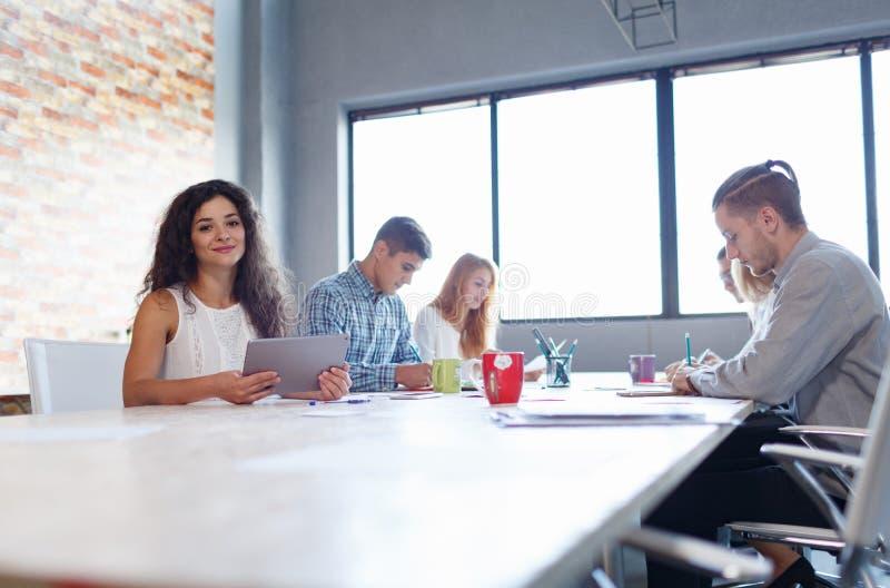 Ελκυστική επιχειρησιακή γυναίκα στη συνεδρίαση με τους συναδέλφους στο υπόβαθρο γραφείων Έννοια συνεδρίασης των γραφείων στοκ εικόνες