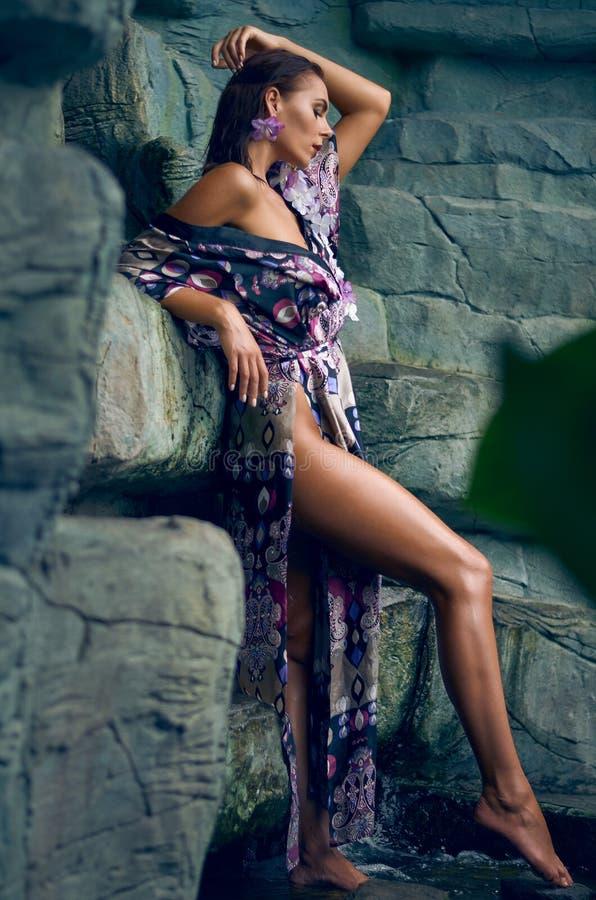 Ελκυστική λεπτή νέα γυναίκα brunette με τα μακριά πόδια που θέτουν σε ένα μακρύ φόρεμα με ένα υψηλό neckline με έναν βράχο στοκ φωτογραφία με δικαίωμα ελεύθερης χρήσης