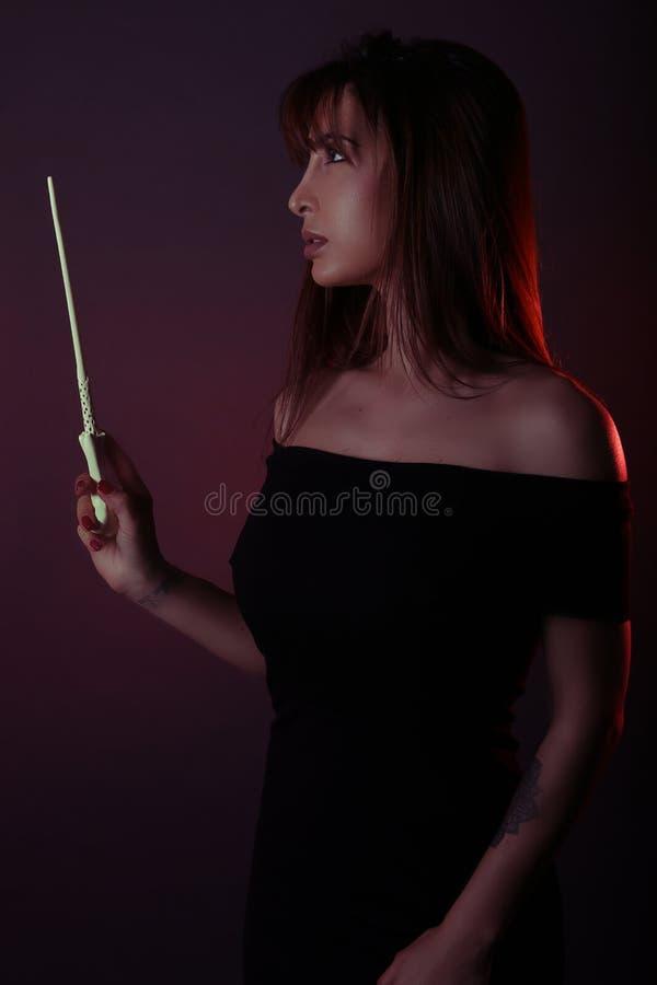 Ελκυστική μάγισσα που κρατά μια μαγική ράβδο στοκ εικόνα με δικαίωμα ελεύθερης χρήσης