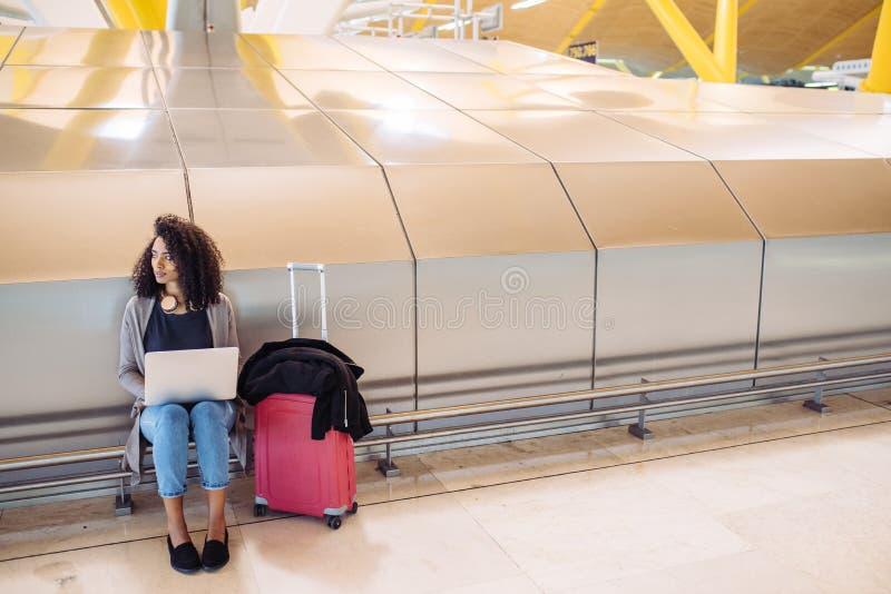 Ελκυστική μαύρη γυναίκα στη συνεδρίαση και την εργασία αερολιμένων με το λ στοκ φωτογραφία με δικαίωμα ελεύθερης χρήσης