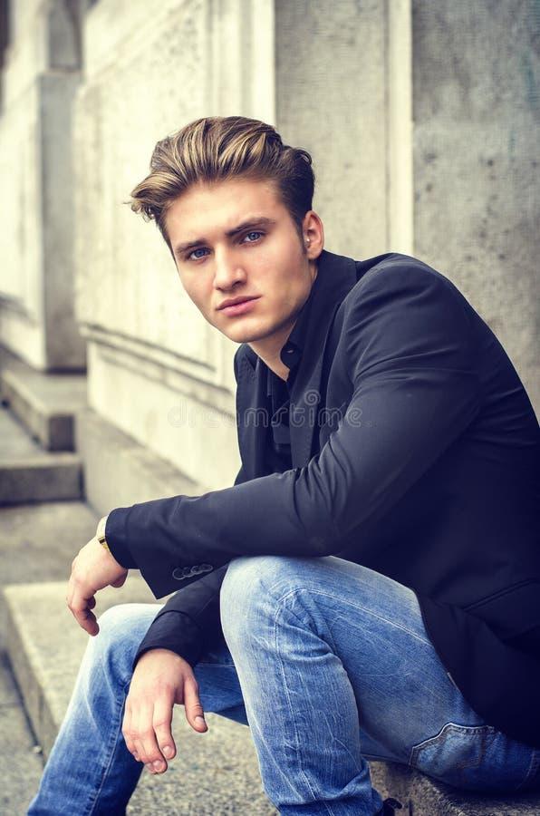 Ελκυστική μπλε eyed, ξανθή συνεδρίαση νεαρών άνδρων στα βήματα σκαλοπατιών στοκ εικόνες