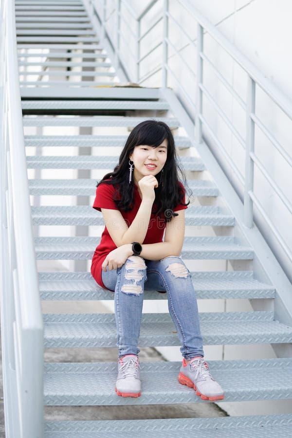 Ελκυστική νέα ασιατική γυναίκα που φορά τα μοντέρνα κόκκινα ενδύματα και την τοποθέτηση Jean στο σκαλοπάτι σιδήρου Ένα πορτρέτο ε στοκ φωτογραφία με δικαίωμα ελεύθερης χρήσης