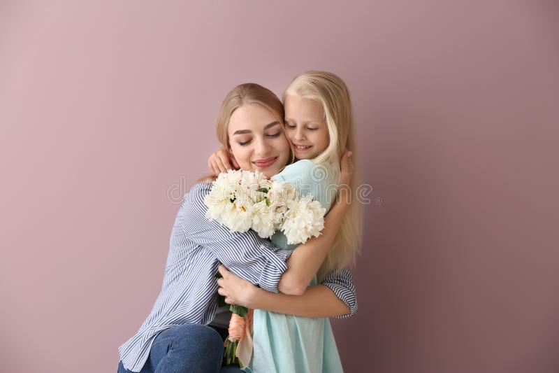 Ελκυστική νέα γυναίκα και χαριτωμένο μικρό κορίτσι με τα όμορφα λουλούδια στο υπόβαθρο χρώματος στοκ εικόνα