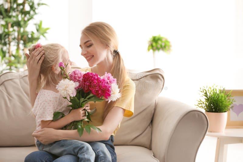 Ελκυστική νέα γυναίκα και χαριτωμένο μικρό κορίτσι με τα όμορφα λουλούδια που κάθονται στον καναπέ στο σπίτι στοκ εικόνα