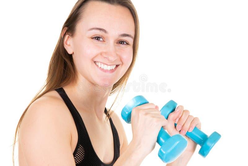 Ελκυστική νέα γυναίκα με τους μπλε αλτήρες που κάνουν crossfit workout στοκ φωτογραφίες