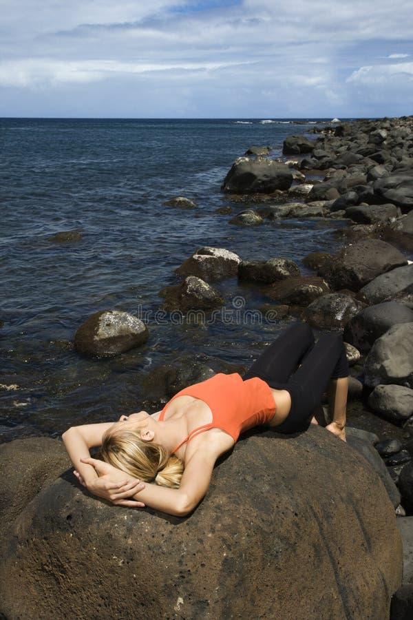Ελκυστική νέα γυναίκα που βρίσκεται στο βράχο στην παραλία στοκ εικόνες